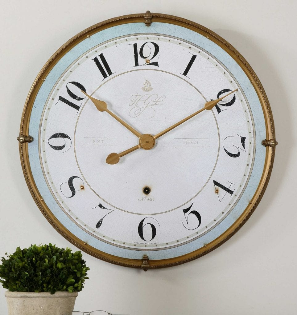"Wall clock featuring an antiqued, gold metal frame with an antiqued ivory face and a pale blue accent around the inner edge. Quartz movement ensures accurate timekeeping. Requires one ""AA"" battery. 32"" Round"