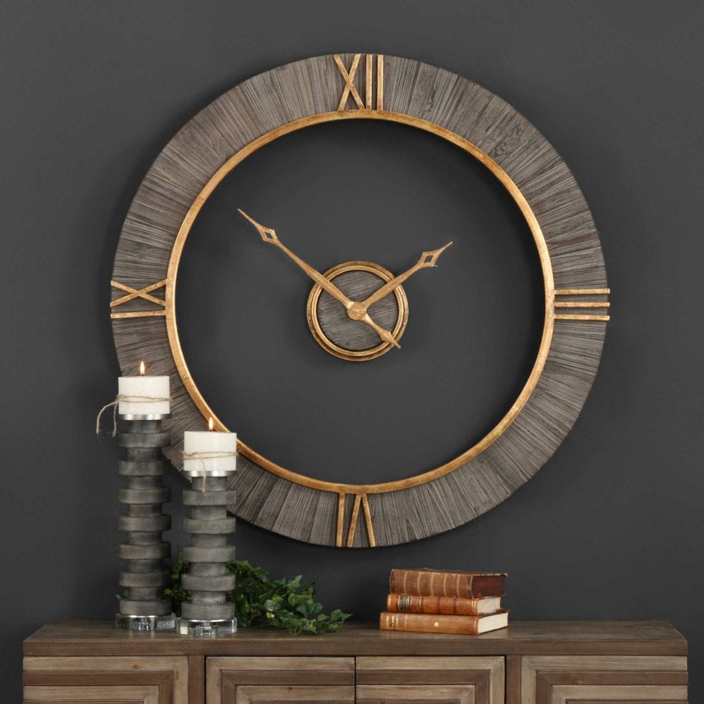 "Wall clock features charcoal stained fir wood with antiqued gold accents and floating center dial. Quartz movement ensures accurate timekeeping. Requires one ""AA"" battery. 39"" Round"