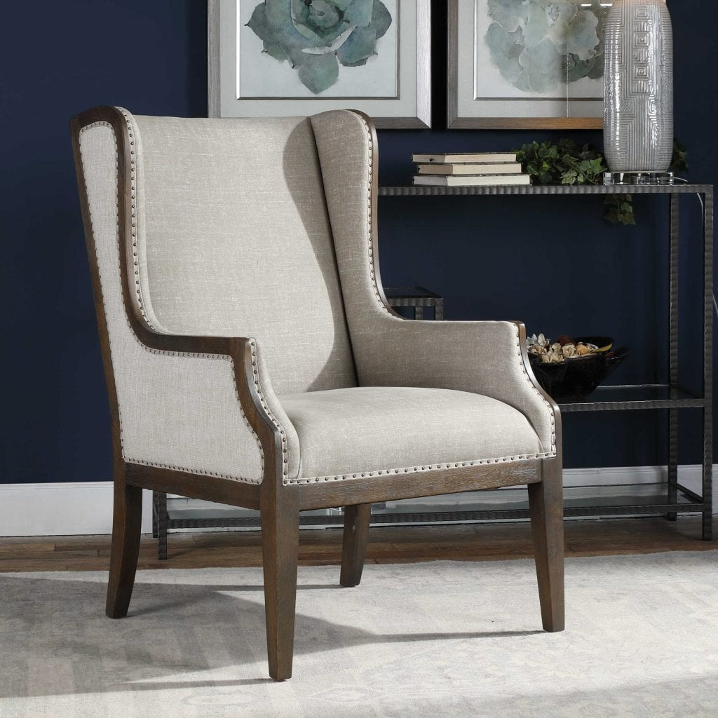 High wing backed chair with antique bronze nail heads, deep walnut stained frame and taupe fabric. REG. $1227 NOW $699
