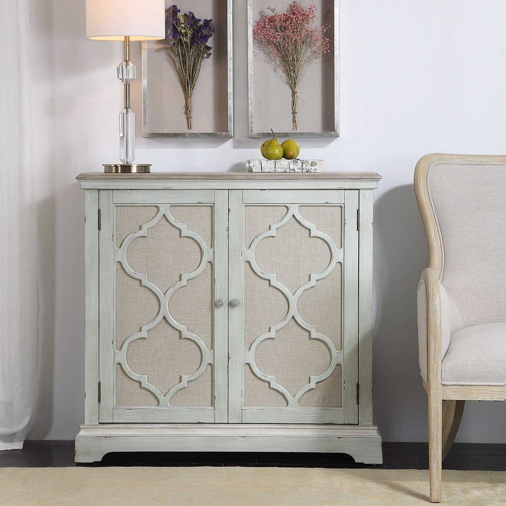 This casual accent cabinet is finished in a weathered sea grey with ivory accents. Open-carved doors are backed in light tan linen, enclosing one adjustable shelf and two storage drawers.