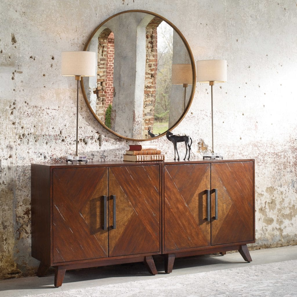 Mid century inspired styling, with geometrically pieced mango veneer doors accented with an ash burl veneer center finished in a deep mahogany stain with natural distress marks and burnishing, complete with antique brass finished bar handles. Includes one adjustable interior shelf.